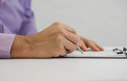 Businessman writes in a notebook while sitting at a desk Stock Photography