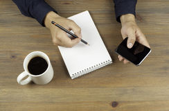 Businessman writes notes in a notebook and use smart phone Stock Images