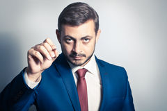 Businessman writes. A pen and looking at the camera Stock Images