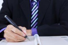 Businessman writes personal organizer Royalty Free Stock Image