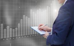 Businessman writes a report and analyzes financial . Stock Photo