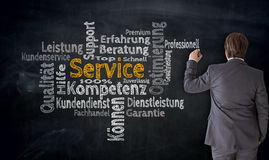Businessman writes service in german Competence, consulting cl. Oud on blackboard concept royalty free stock image