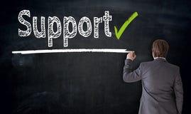 Businessman writes support on blackboard concept stock photo