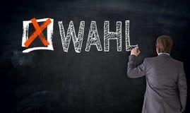 Businessman writes Wahl in german Vote on blackboard concept Royalty Free Stock Photos