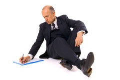 Businessman writing. Businessman sitting on the floor and writing. isolated on white Stock Images