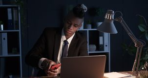 Businessman writing on adhesive note and sticking it on laptop at night stock footage