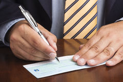 Businessman Writing Blank Check Ballpoint Tie. Close up of businessman or salesman hand writing signing blank check with silver ballpoint stock images
