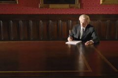 Businessman Writing In Boardroom Stock Photo
