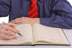 Businessman writing in book. Isolated over white background Royalty Free Stock Photography