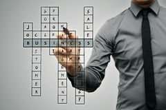 Businessman writing business concept by crossword Stock Images