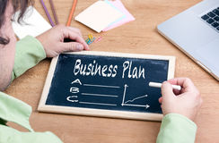 Businessman Writing Business Plan Growth Concept. Chalkboard on. Wooden office desk Stock Photo