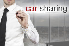 Businessman writing car sharing in the air Stock Photo