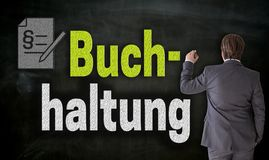 Businessman is writing with chalk Buchhaltung in german accounting on blackboard stock photo