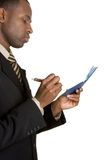 Businessman Writing Check. African american businessman writing check Royalty Free Stock Photo