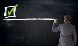 Businessman writing checkbox on blackboard concept stock photo