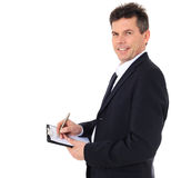 Businessman writing on clipboard Stock Image