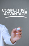 Businessman writing competitive advantage with a marker. On grey background stock image