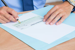 Businessman writing a contrat before signing it Stock Images