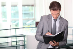 Businessman writing in diary. Businessman writing in his diary Royalty Free Stock Photo