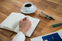 Businessman writing on a diary. In office Royalty Free Stock Images