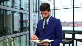 Businessman writing in diary at office stock video