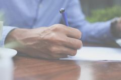 Businessman writing document. Close up. Focus is on hand Stock Photo