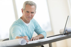 Businessman Writing On Document At Desk Stock Images