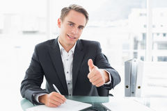 Businessman writing documents and gesturing thumbs up at office desk Stock Image