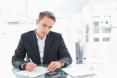 Businessman writing documents at office desk Royalty Free Stock Images