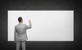 Businessman writing or drawing on white board Royalty Free Stock Image