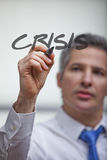 Crisis management. Middle-aged business man writes the word crisis on a transparent board with a felt tip Stock Photos