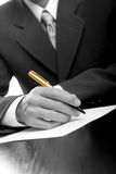 Businessman writing on a form. B/W & Gold pen stock photos