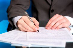 Businessman writing on a form. Businessman writing on a business form royalty free stock photography