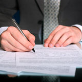 Businessman writing on a form. Businessman writing on a business form royalty free stock photo