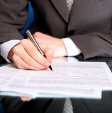 Businessman writing on a form. Businessman writing on a business form royalty free stock images