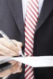 Businessman writing on a form Stock Photos