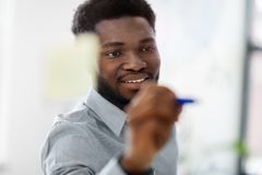 Businessman writing on glass board at office. Business and people concept - close up of african american businessman writing something on glass board at office Stock Photo