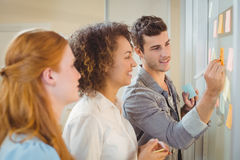 Businessman writing on glass wall as female colleagues looking at it. During meeting in office stock images