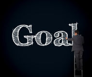 Businessman writing goal on a giant blackboard Stock Images