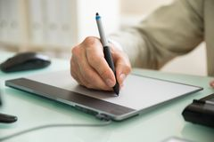Businessman writing on graphic tablet Stock Photos