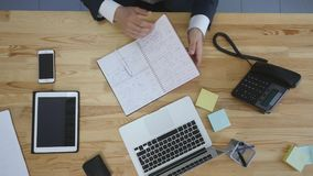 Businessman writing his to-do list, male planning day in office, top view.  Stock Photo
