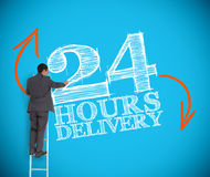 Businessman writing 24 hours delivery. On a blue background Royalty Free Stock Photography