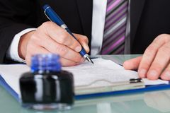Businessman Writing With Ink Pen. Close-up Of Businessman Hand Writing With Ink Pen Over Document Stock Image