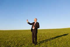 Businessman Writing On Invisible Screen On Field Stock Images