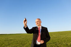 Businessman Writing On Invisible Screen With Marker On Field Royalty Free Stock Photo