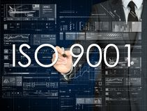 The businessman is writing ISO 9001 on the transparent board wit Royalty Free Stock Photography