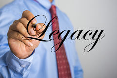 Businessman writing Legacy word on virtual screen Stock Photo