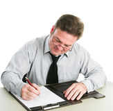 Businessman Writing on Legal Pad. Businessman looking down and taking notes on a legal pad.  White background Royalty Free Stock Photo