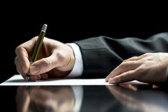 Businessman writing a letter or signing. Businessman writing a letter, notes or correspondence or signing a document or agreement, close up view of his hand and Stock Images