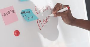 Businessman writing a message on whiteboard at office. Hand of african american businessman writing a message on whiteboard at office stock footage